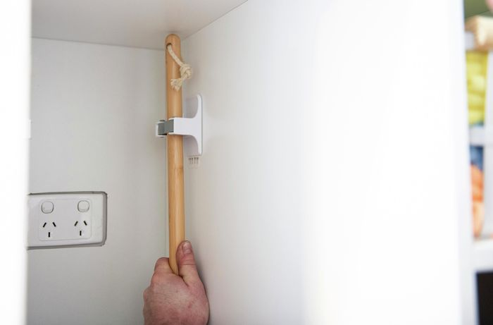 Person hanging broom in cupboard