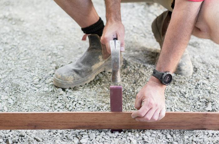Person hammering in an edging peg next to a length of timber edging on a gravel base.