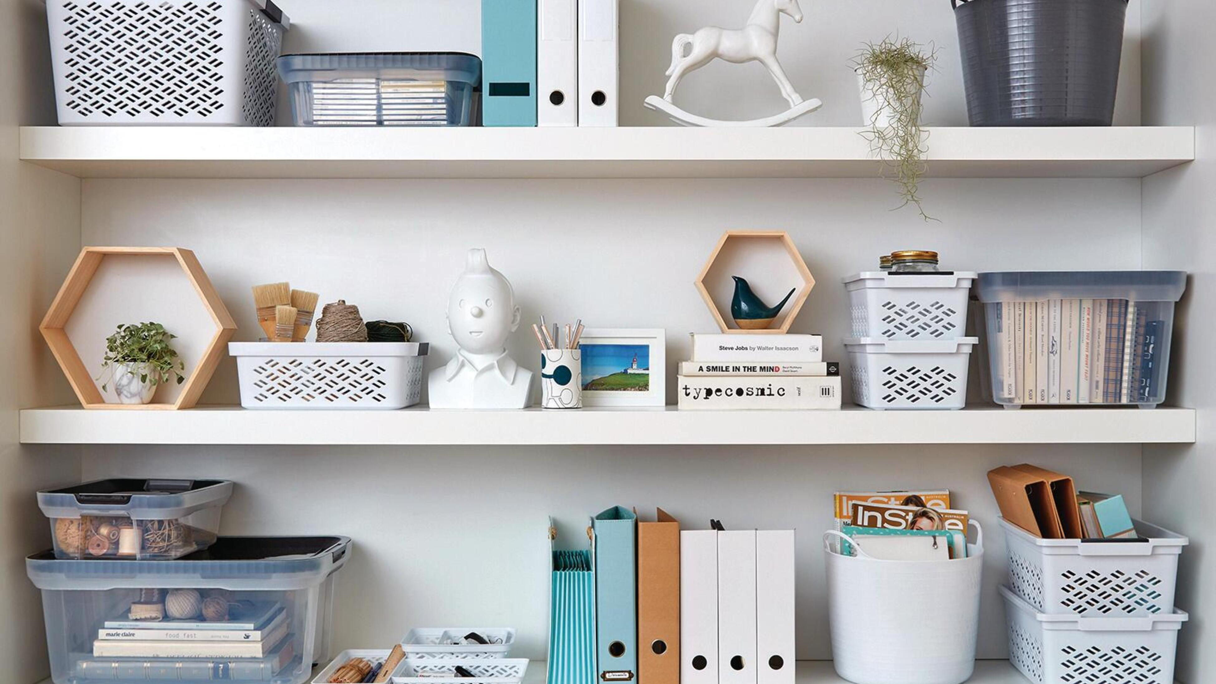A neatly styled shelf with folders and storage boxes.