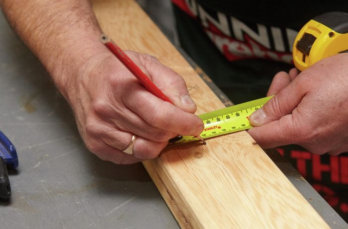 Person using tape measure and pencil to make a mark on timber.