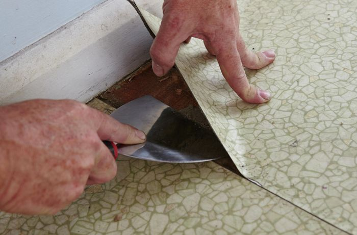Person prying vinyl flooring from the ground