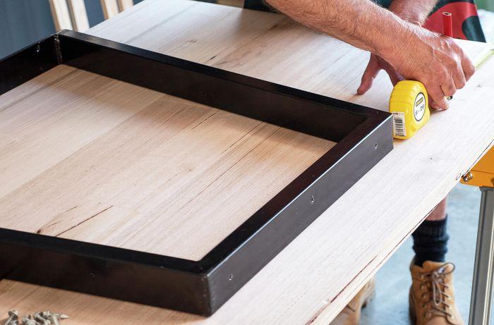 Metal frames being used as desk legs being measured against the desk top