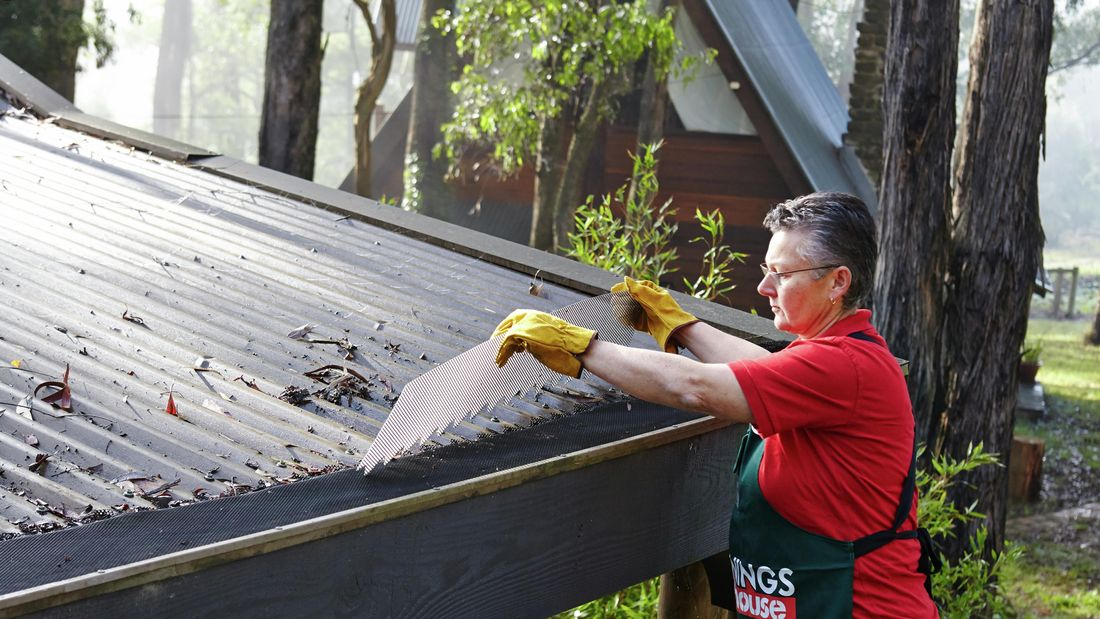 Person fitting gutter guard to a roof in a bushland setting