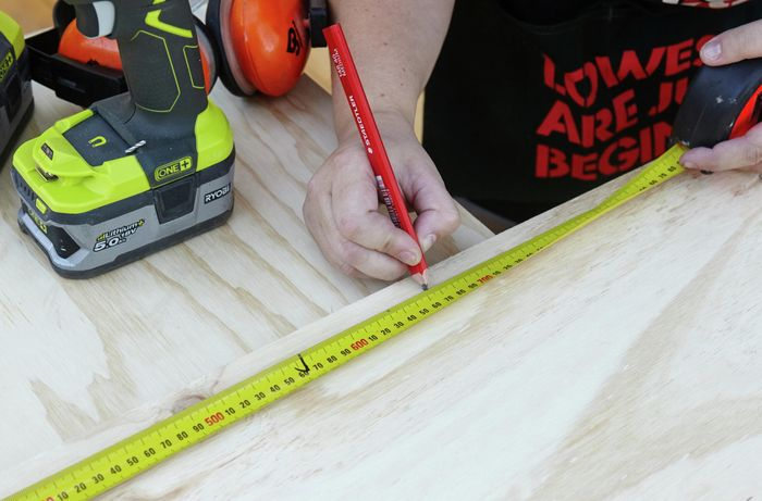 A pencil and tape measure being used to mark a panel of wood