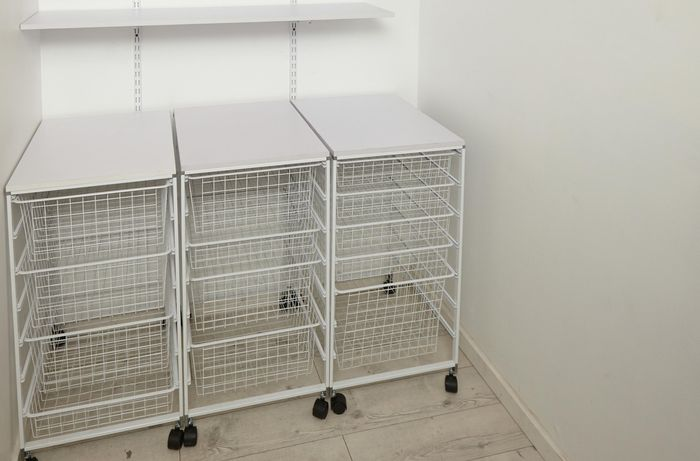 A linen closet with wire baskets trolleys