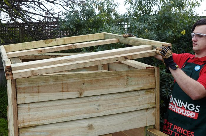 A roof frame being lowered onto a chicken coop by a Bunnings team member