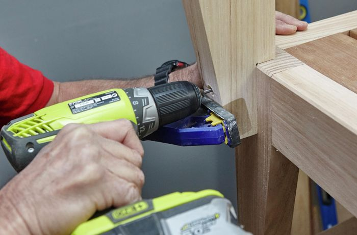 Backrests being attached to a wooden chair with a power drill, while a clamp holds it in place