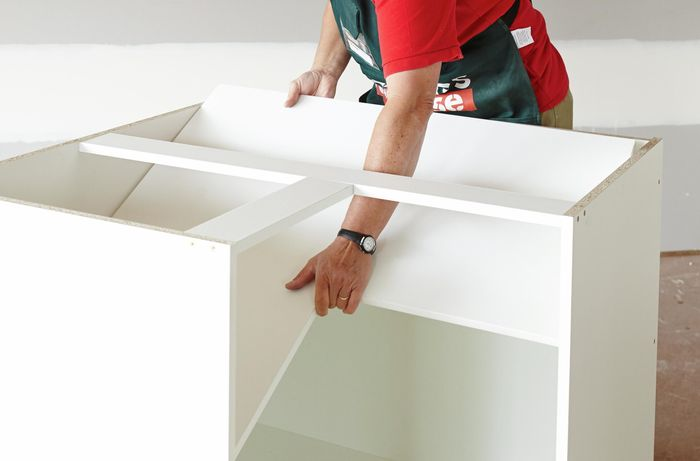Person placing shelf into cabinet