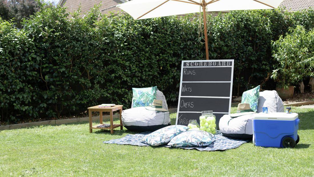 Chalk scoreboard in a backyard leaning on an umbrella
