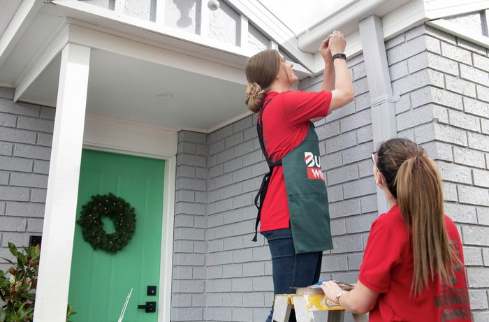One person holding a stepladder while another person hangs a gutter hook at the front of a house