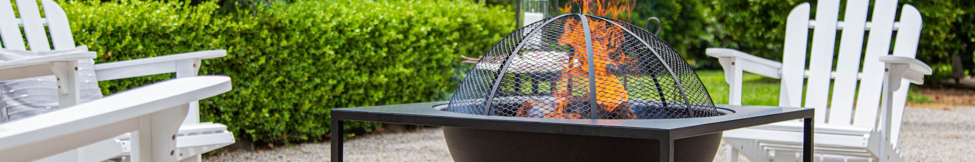 A Glow outdoor fire pit surrounded by outdoor chairs.