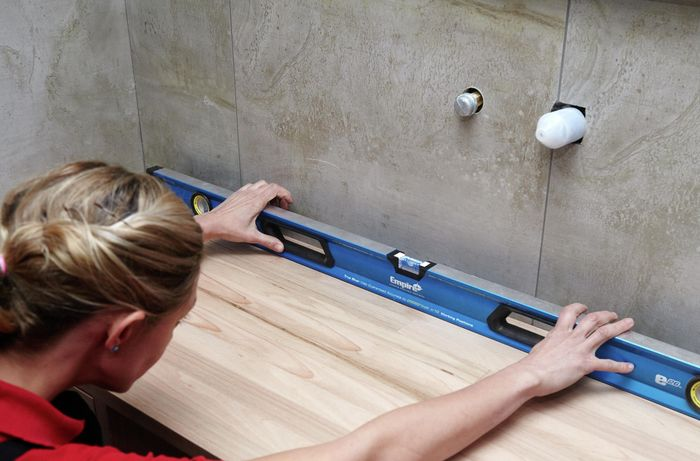 A person checking a timber vanity alignment with a spirit level