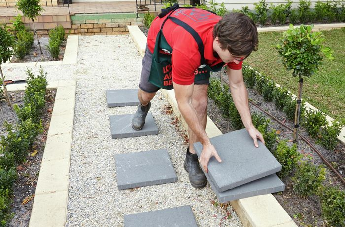A person lifting a paver from a stack with other pavers laid out along a gravel path
