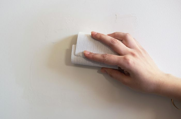 Using a sandpaper block to sand and clean the area