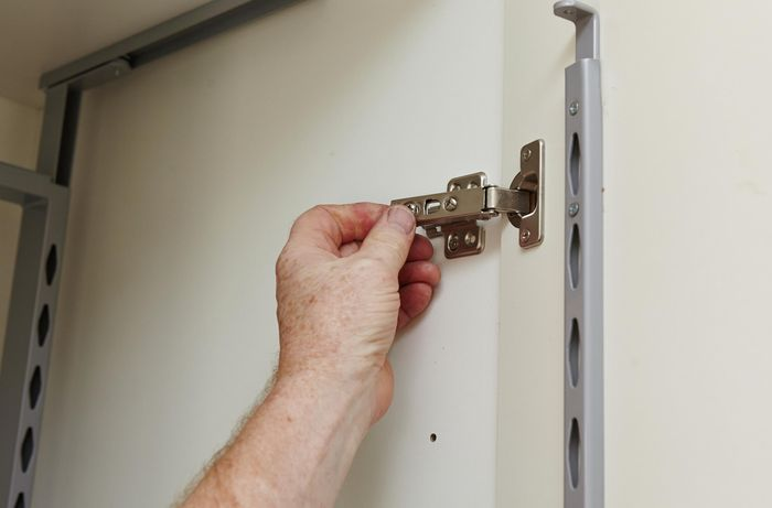 A door being hung on a pantry on push to open hinges