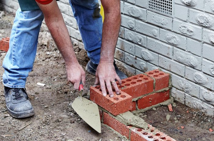A person laying a second course of bricks parallel to a house wall