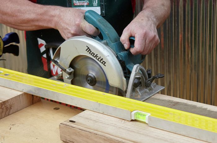 Person cutting bit of timber with circular saw.
