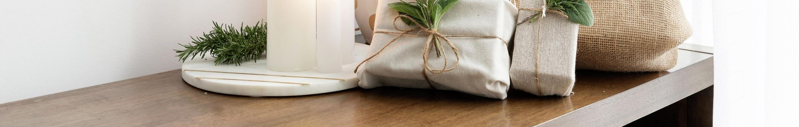 Gifts wrapped with hessian and decorated with rosemary, white candles and a mini Christmas tree.