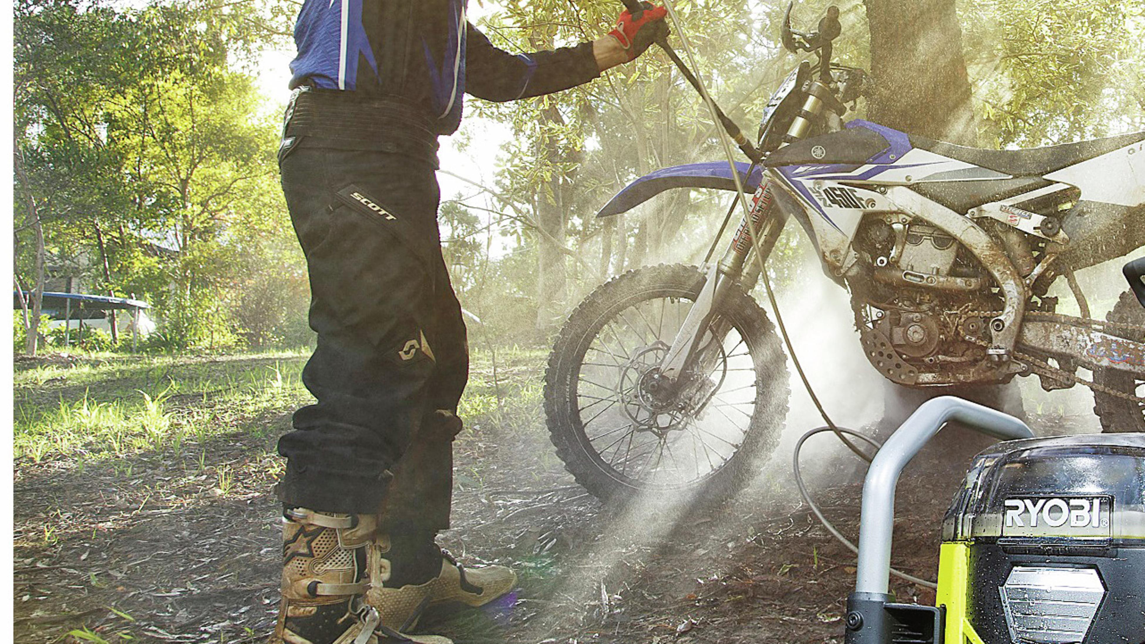 A pressure washer cleans a dirt bike.