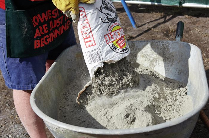 Dry concrete being emptied into a wheelbarrow