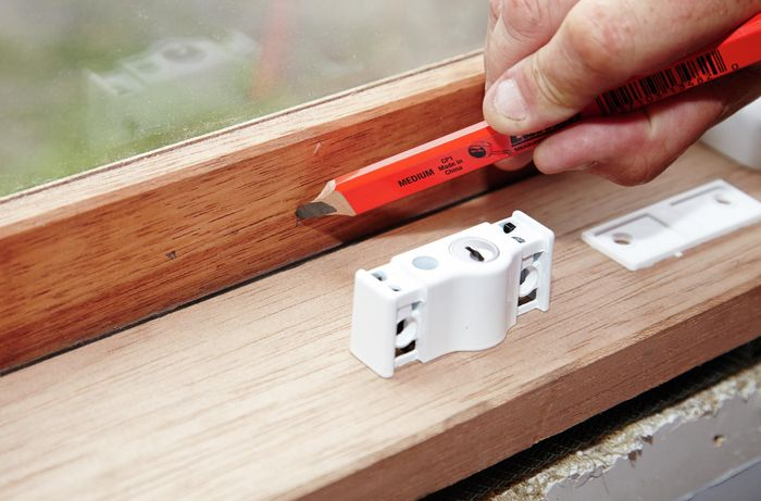 A person marking a window frame with a pencil