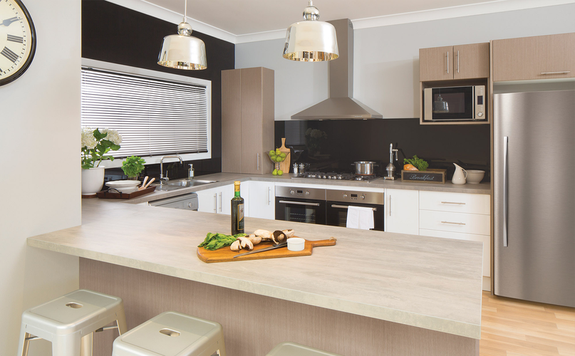 Kitchen with timber benchtops, two ovens, a stove and range hood