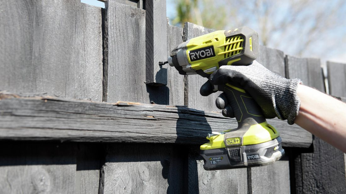 Person uses a cordless drill to drill a hole into a fence post.