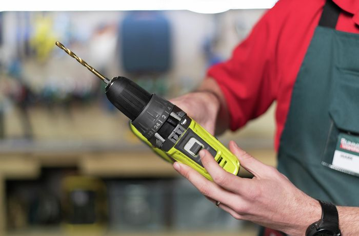 Team member showing the controls on a power drill