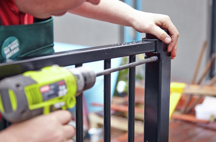 Person drilling into an aluminium fence.