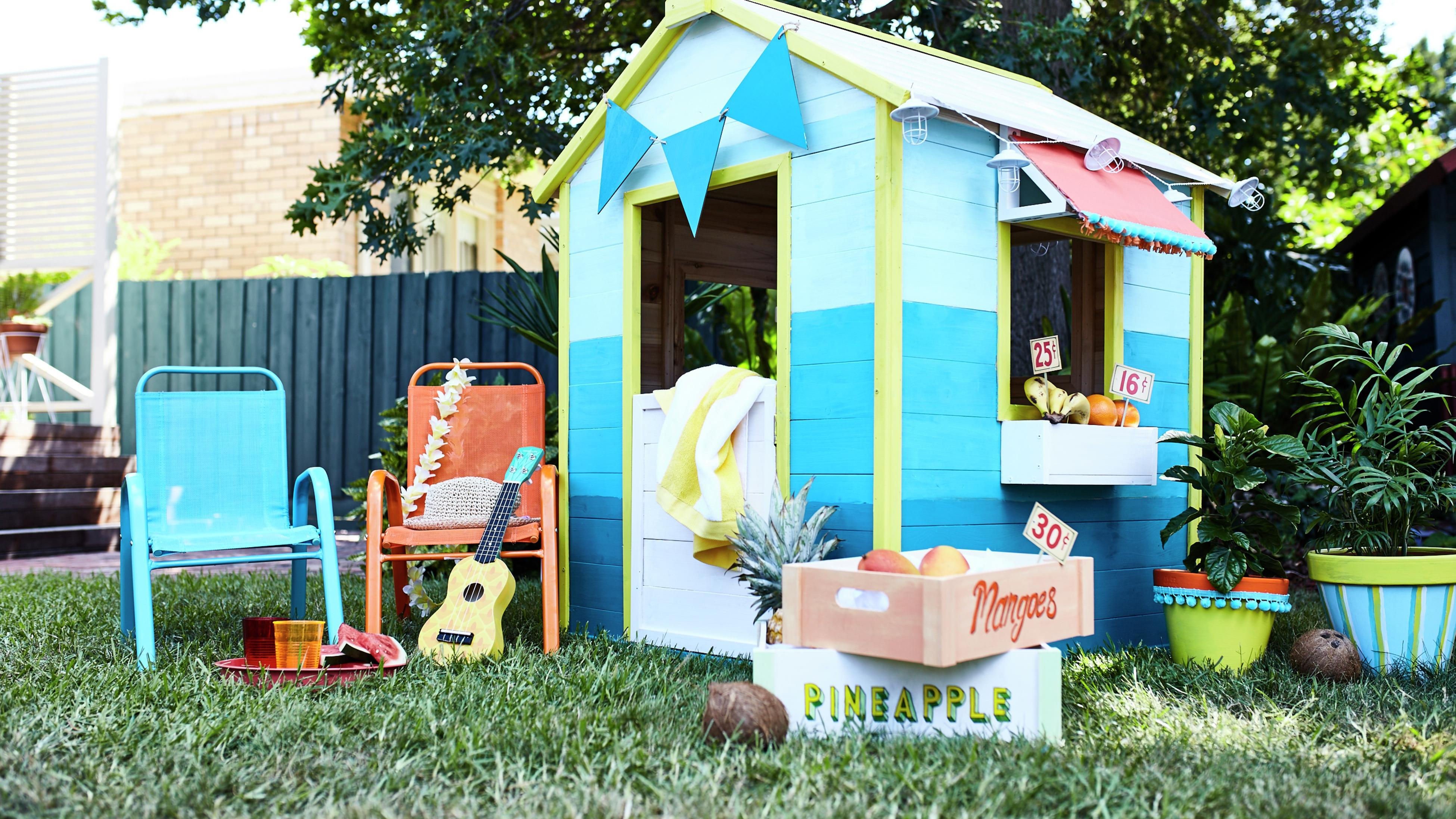 Kids cubby house with small recliner chairs, and decorative items out front.