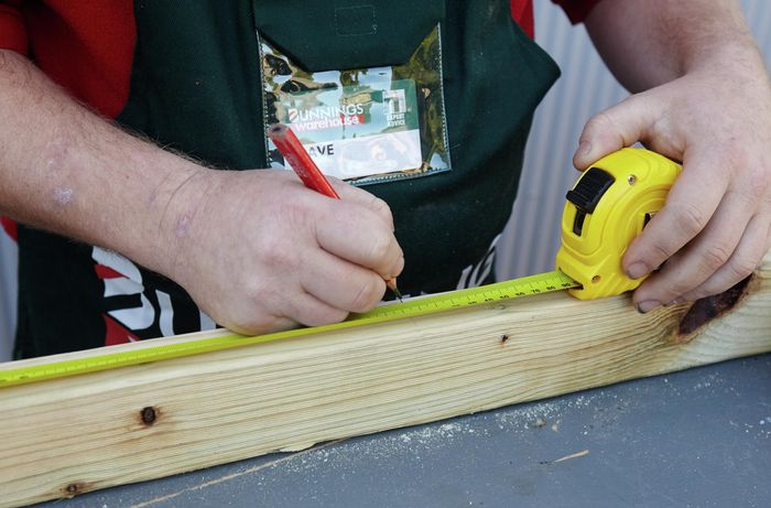 Person measuring piece of timber and marking it up with pencil and tape measure.