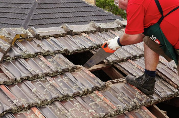 A tile batten being sawed through by a Bunnings team member standing on the roof