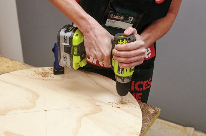 A person drilling a hole in a round sheet of plywood using a cordless drill