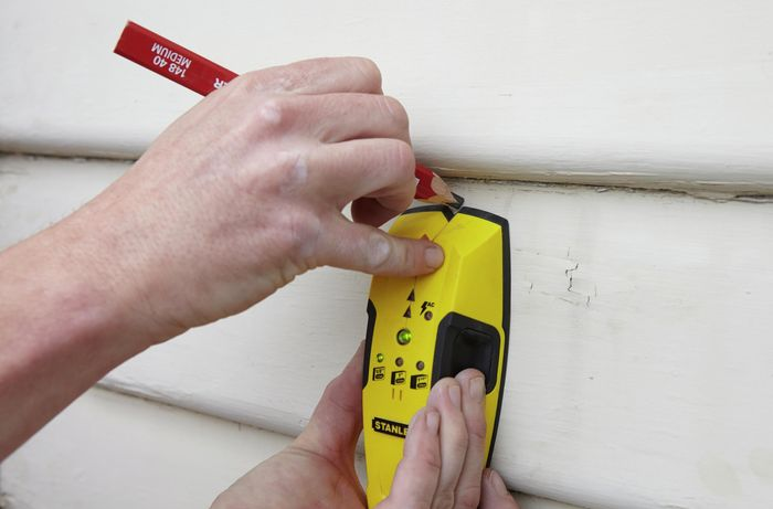 A stud finder being used to locate the stud wall behind weatherboards