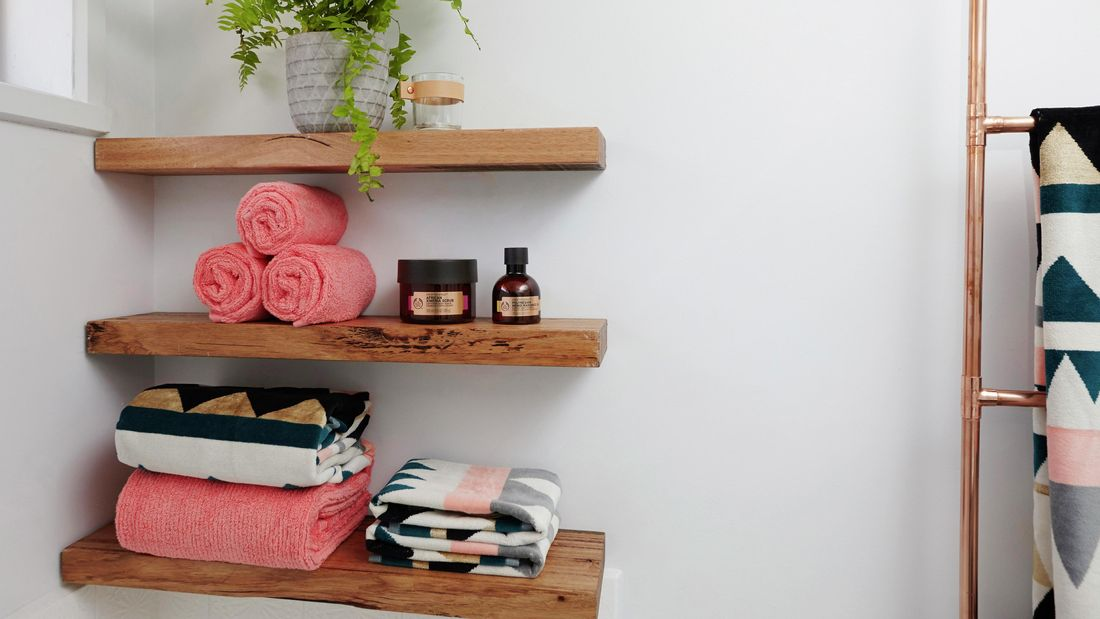 Timber wall shelves with towels and bathroom products sitting on them.