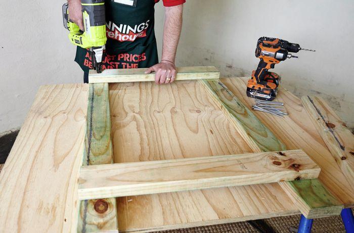 A person using a nail gun to assemble a timber frame