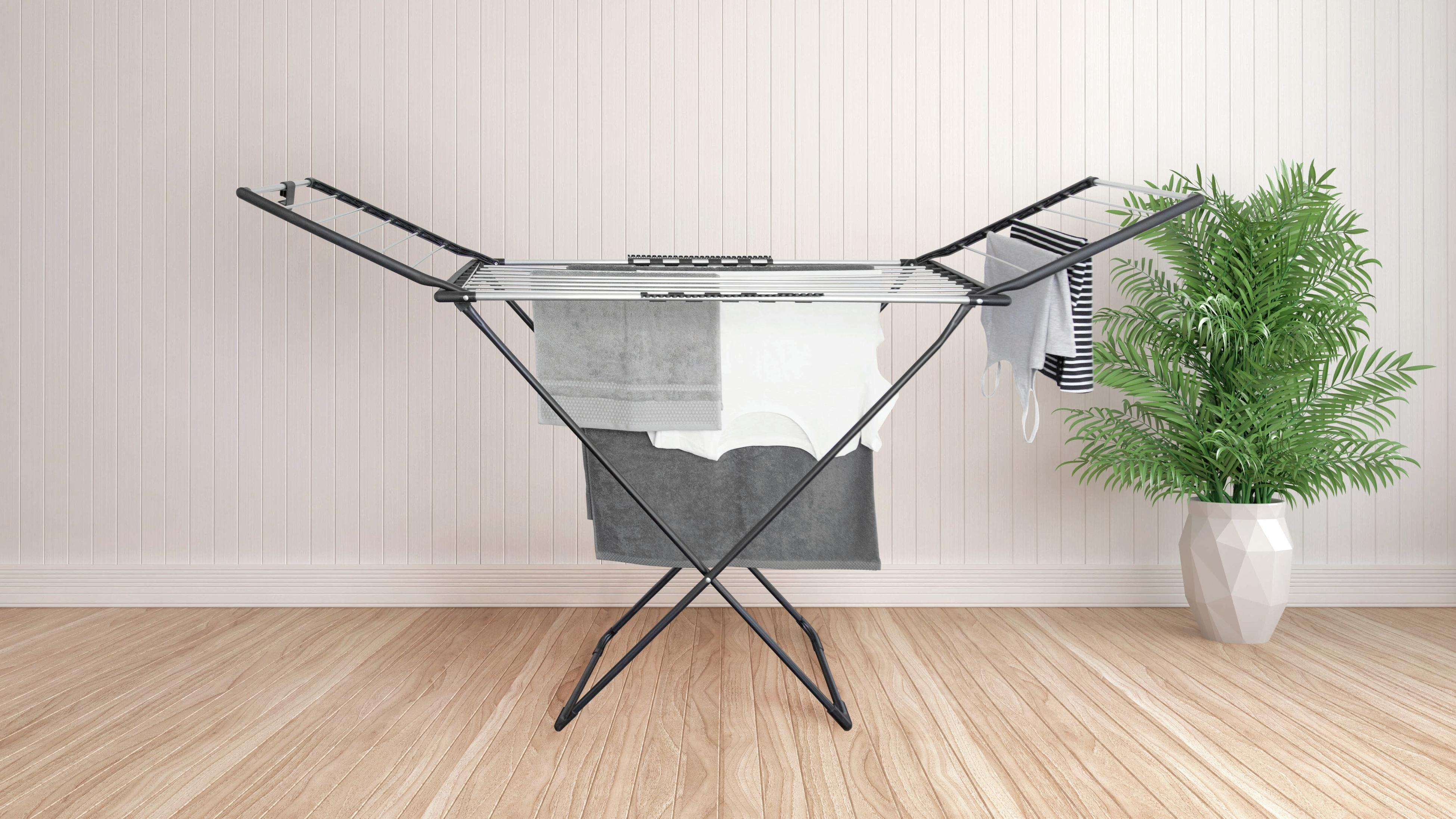 Portable clothes drying rack with clothes on it in a living room