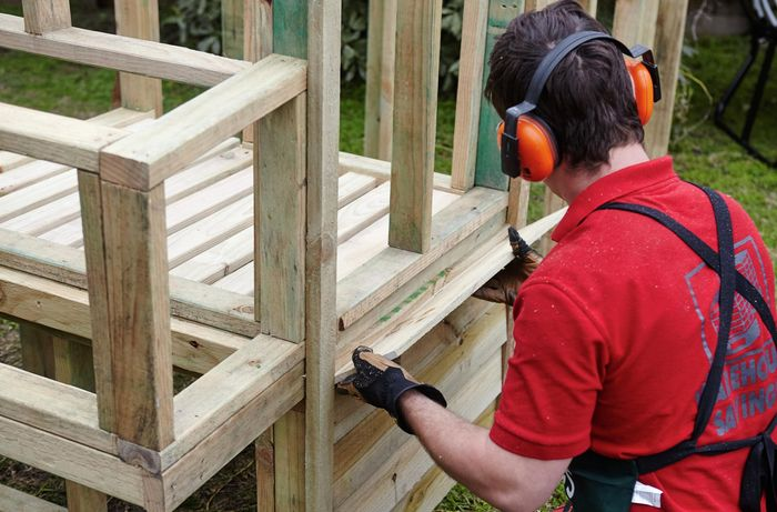 The entrance to the roosting coop being attacked to the wooden frame by a Bunnings team member