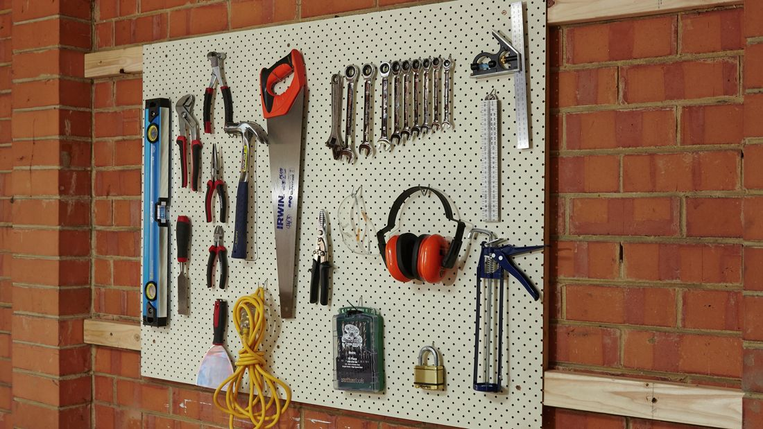 A completed pegboard tool holder mounted on a brick wall