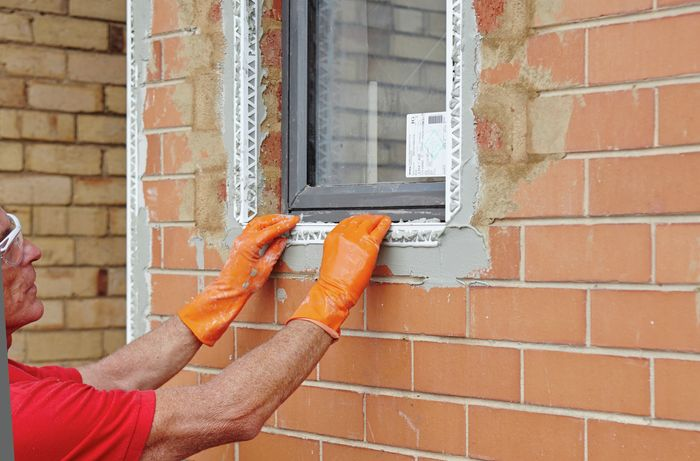 A person placing bead into render around a window in a brick wall