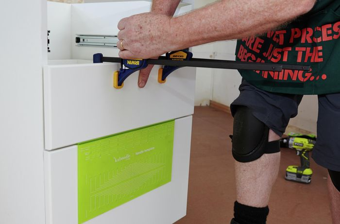 Person using clamps to install cabinet panels