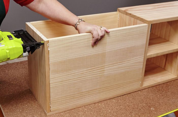The storage space of a kids' bench being assembled with a power drill