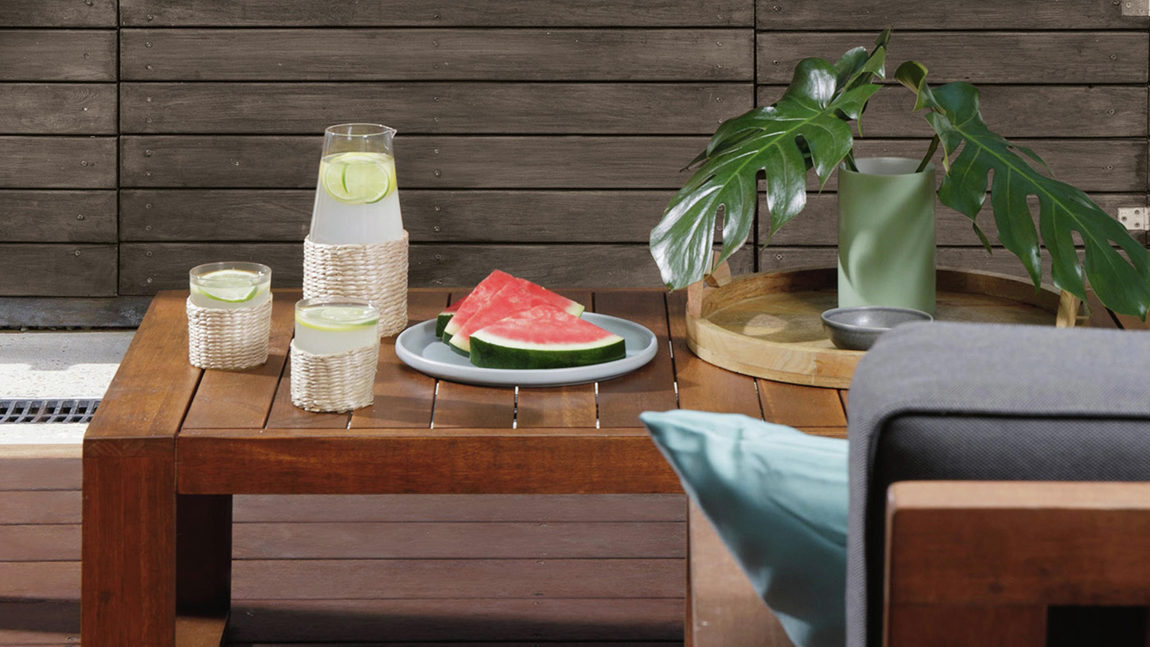 Dining table in outdoor dining area with watermelon and lemonade