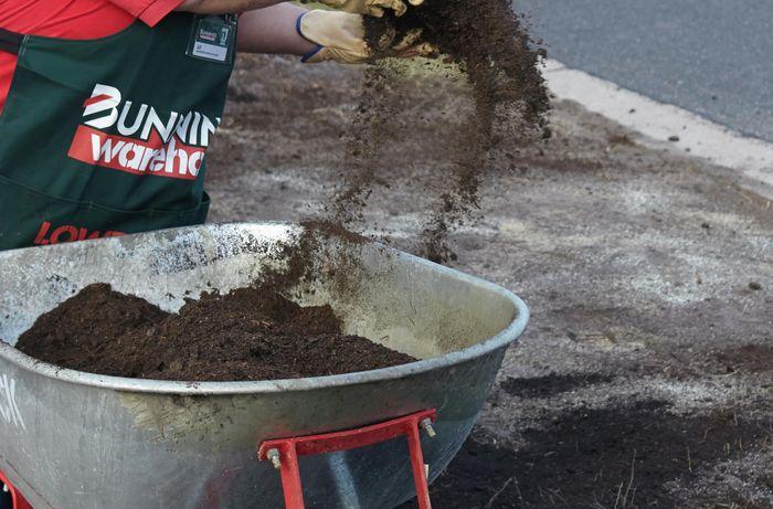 A person spreading soil from a wheelbarrow onto the ground