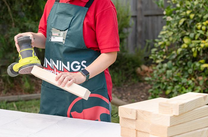 Bunnings team member sanding the end of a piece of timber with an orbital sander