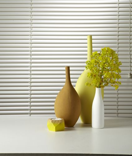 Close up of vases and a candle in front of a window with white venetian blinds