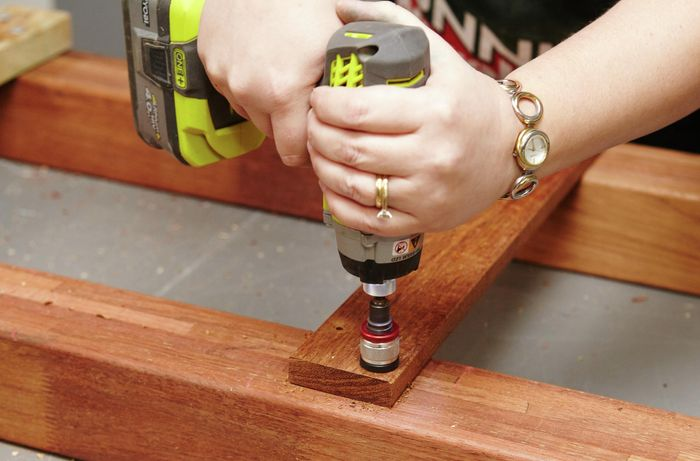 Person drilling spacer to wooden table legs.