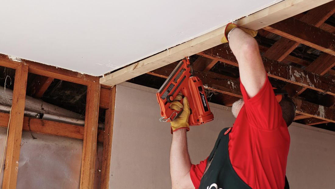 Person installing stud wall top plate.