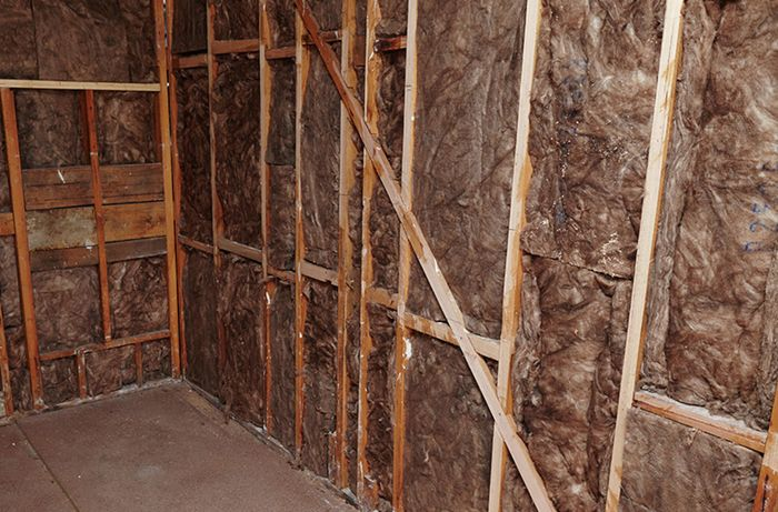 An indoor room with bare walls lined with insulation