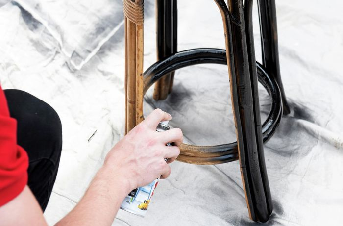 Person spray painting a cane bar stool with black paint